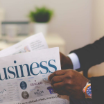 person reviewing a business newspaper